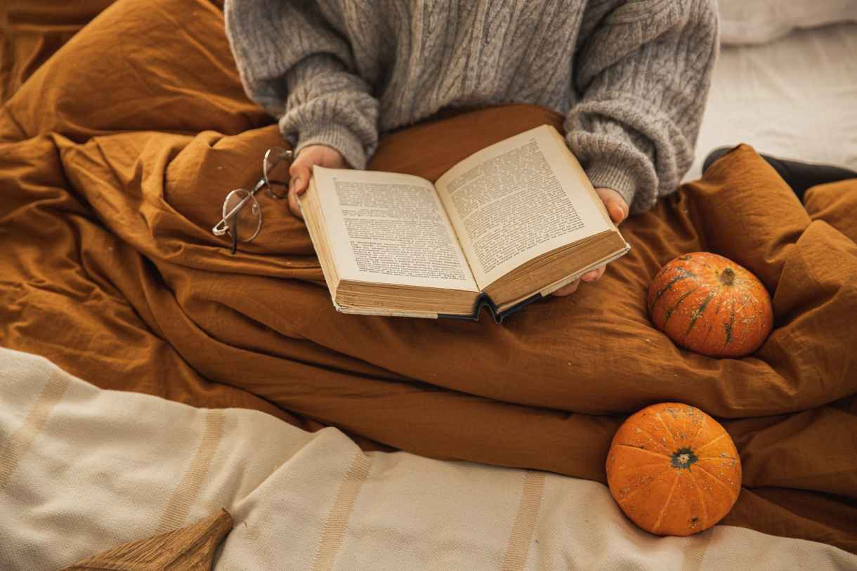 A girl reading a book with an orange blanket around her and pumpkins.