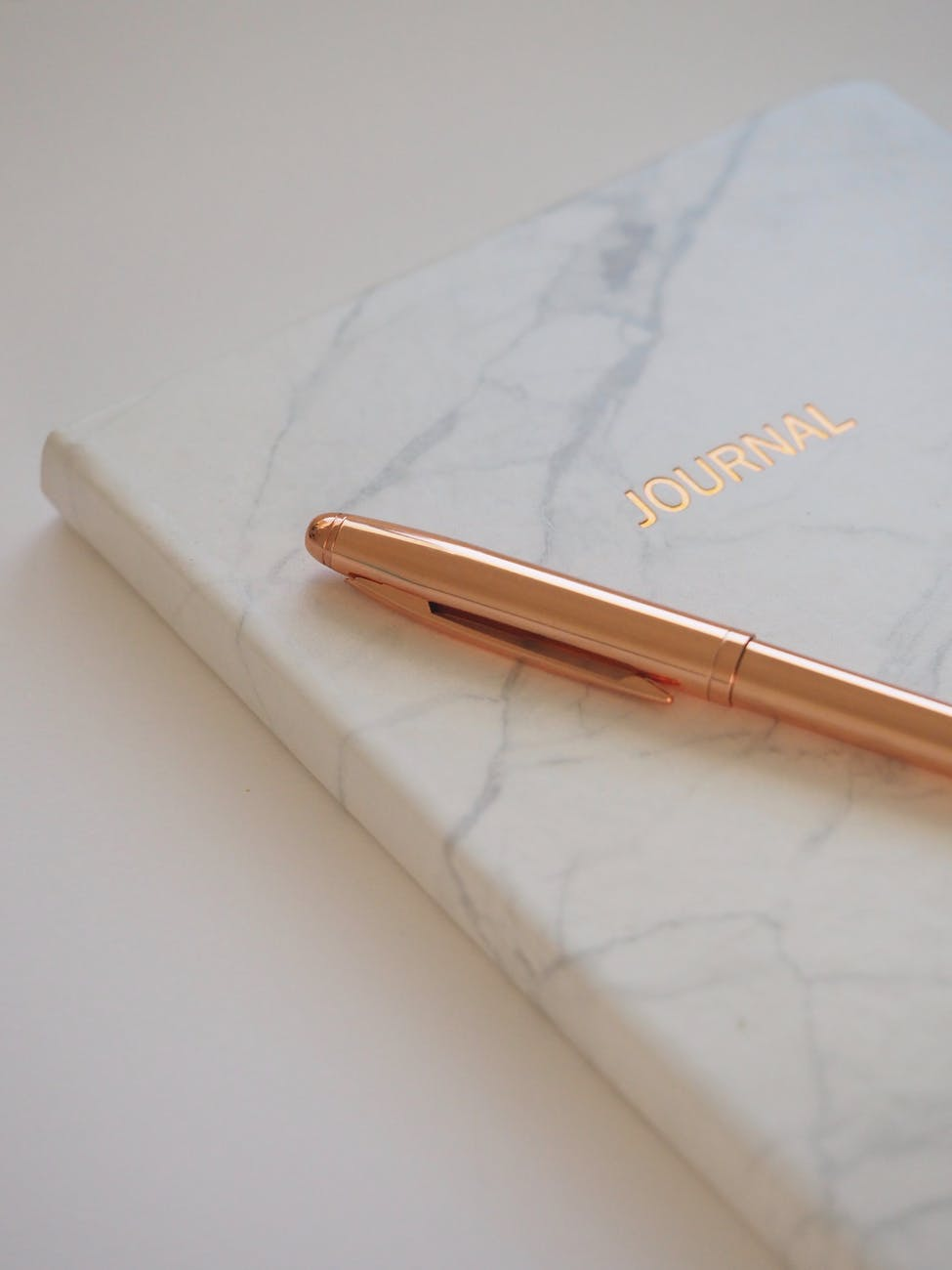 A white journal with a gold pen