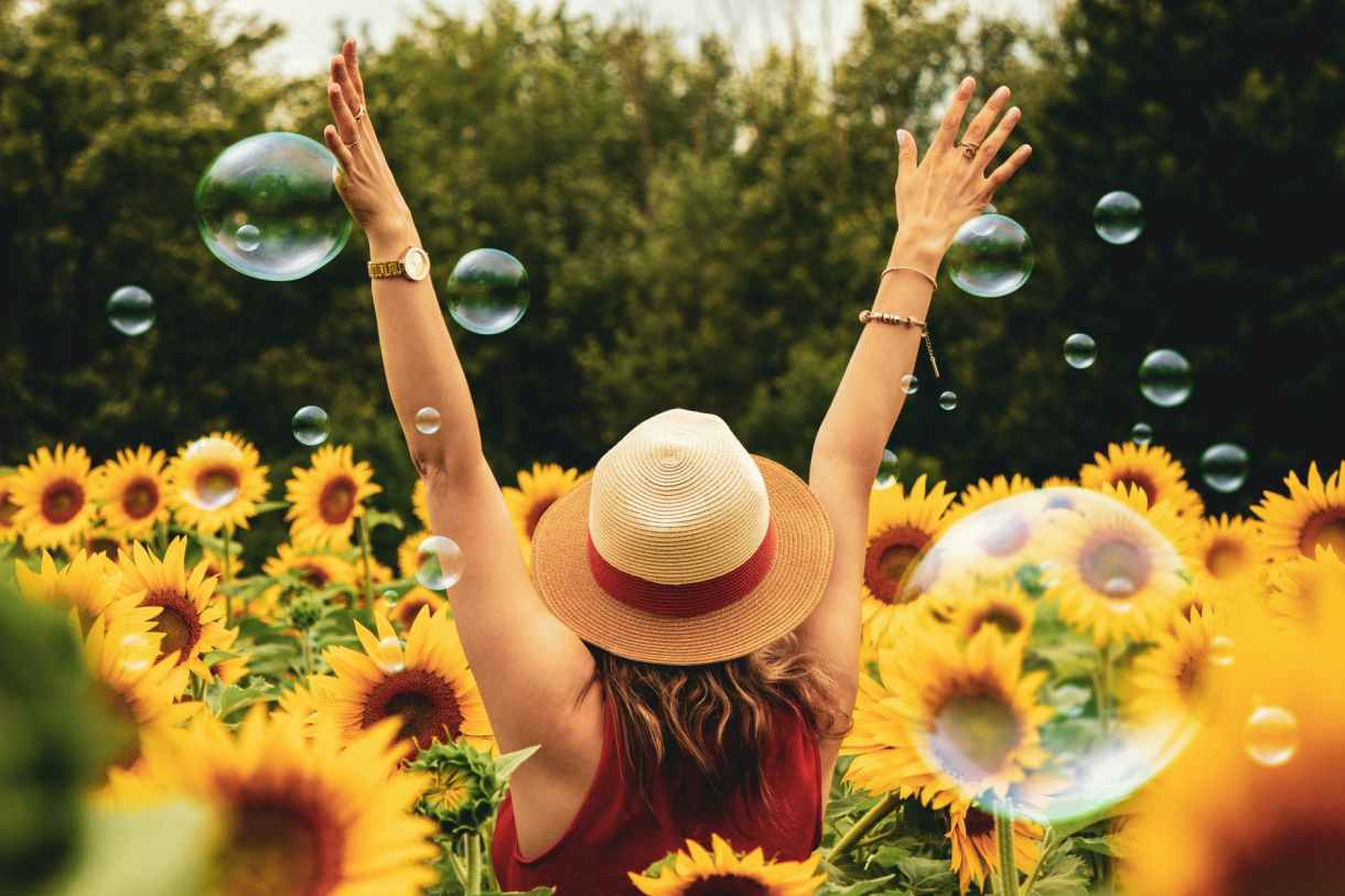 A happy woman in a sunflower garden with bubbles