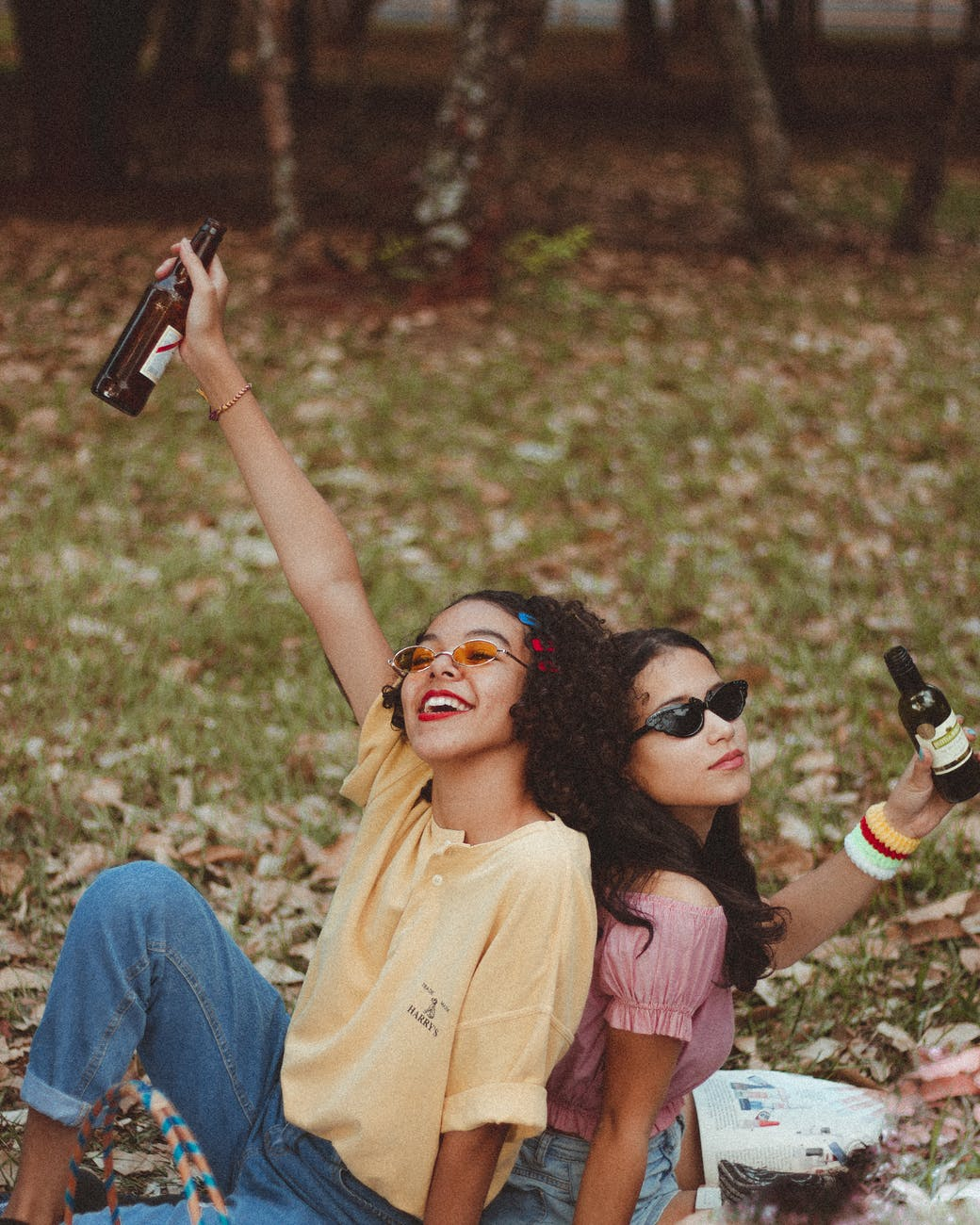Two girlfriends sitting down with a bottle of drink in their hands